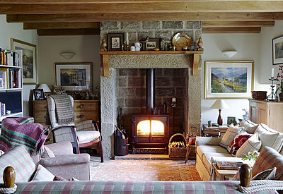 Lit woodburner in exposed stone fireplace with seating area in Hexham country house - p349m790386 by Brent Darby