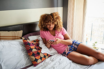 Black woman laying on bed texting on cell phone - p555m1231798 by Granger Wootz