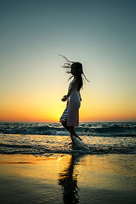 Girl Dancing on Beach at Sunset  - p1019m1467948 by Stephen Carroll