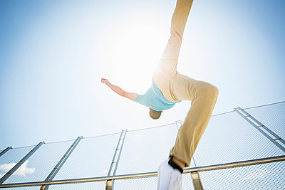 Young man somersaulting on a bridge.  - p1100m1038920 by Mint Images