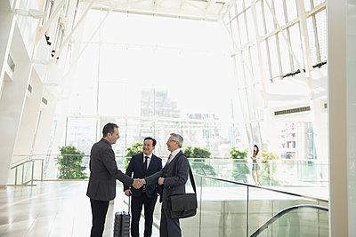 Businessmen handshaking in airport atrium - p1192m1231129 by Hero Images