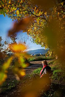 Frau sitzt auf einer Bank bei schönem Herbstwetter - p227m1503294 von Uwe Nölke