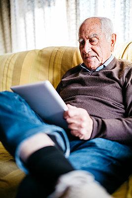 Senior man sitting on couch using tablet - p300m1205897 by Josep Rovirosa