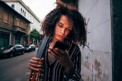 Close-up of man with curly hair holding guitar while using smart phone in city - p300m2206892 by Eugenio Marongiu