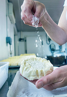 Woman's hand sprinkling flour on cheese at dairy - p300m2225017 by LOUIS CHRISTIAN