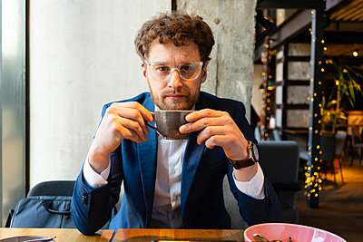 Businessman wearing suit while having coffee at cafe - p300m2268303 by Vasily Pindyurin