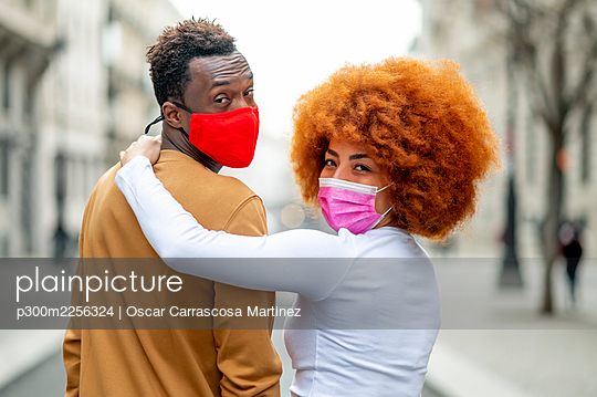 Woman wearing face mask with arm around on man standing outdoors - p300m2256324 by Oscar Carrascosa Martinez