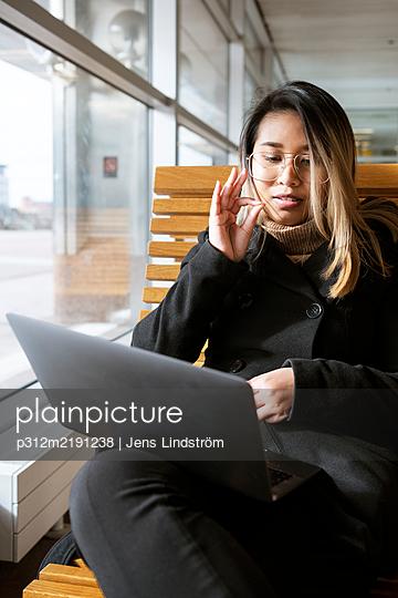 Woman at train station using laptop - p312m2191238 by Jens Lindström