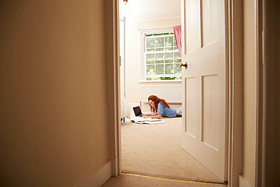 Preteen girl doing homework at laptop on bedroom floor - p1023m2238505 by Himalayan Pics