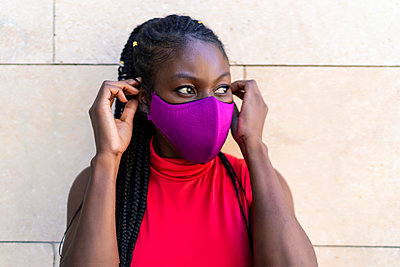 African woman athlete putting on the mask - p1166m2269216 by Cavan Images