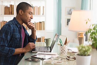 Black businessman working on laptop at desk - p555m1412824 by JGI/Tom Grill