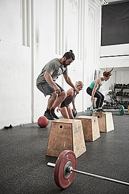 Friends jumping onto fitness box in cross training gym - p924m1468855 by Jakob Helbig