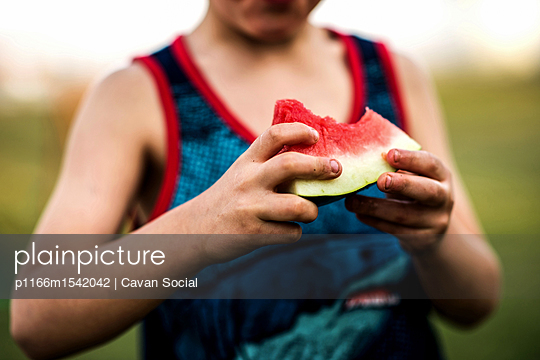 Midsection of boy eating watermelon - p1166m1542042 by Cavan Social