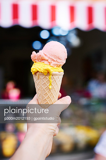 Woman's hand holding ice cream cone with two scoops - p300m2012193 von gpointstudio