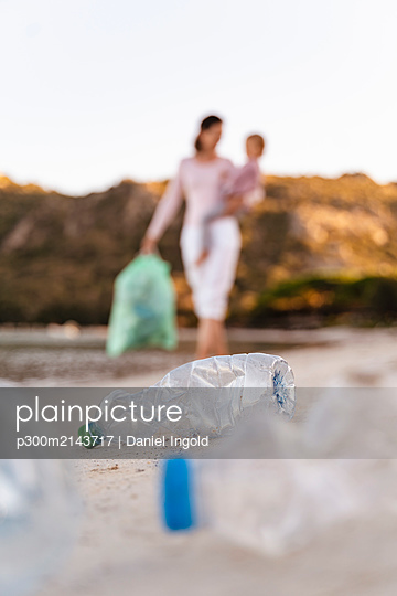 Woman with children on her arm collecting empty plastic bottles on the beach - p300m2143717 by Daniel Ingold