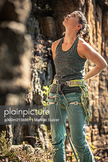 Woman preparing to climb, looking up on climbing wall - p300m2156561 by Manuel Sulzer