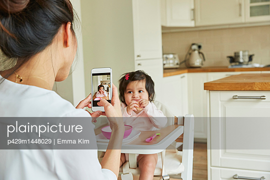 Over shoulder view of woman photographing baby daughter in high chair - p429m1448029 by Emma Kim