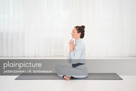 Woman practicing yoga in gym - p430m2244441 by R. Schönebaum