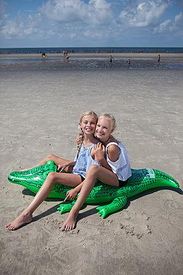zwei Mädchen sitzen auf aufblasbarem Krokodil - p045m1591072 von Jasmin Sander