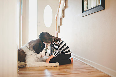 Girl playing with Saint Bernard at home - p1166m1230446 by Cavan Images