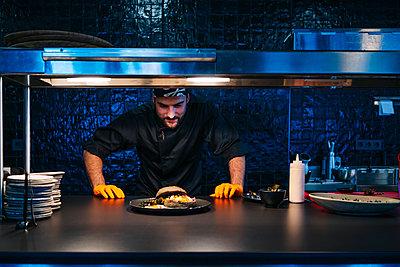 Chef looking at prepared dish in restaurant kitchen - p300m2166743 by Daniel González