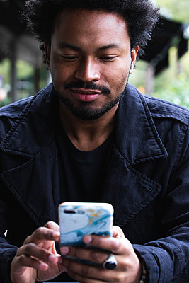 Close-up of handsome man using mobile phone while sitting at sidewalk cafe - p300m2243320 by NOVELLIMAGE
