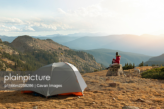 Woman sitting on rock while camping with dog on mountain against sky during vacation - p1166m2258286 by Cavan Images