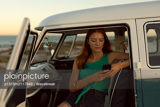 Beautiful woman using mobile phone on front seat of camper van at beach - p1315m2117849 by Wavebreak