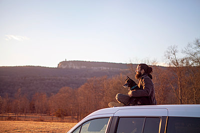 Side view of man sitting with dog on car roof against clear sky - p1166m1473533 by Cavan Images