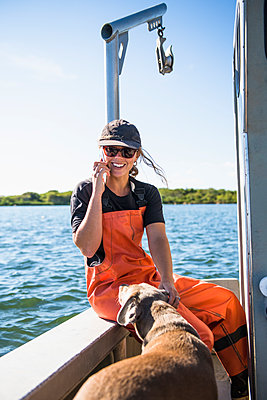 Woman on Phone while working on the water in aquaculture oyster farm - p1166m2268895 by Cavan Images