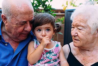 Grandparents looking at baby girl sucking thumb - p300m2029079 von Gemma Ferrando