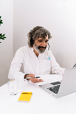 Senior businessman with headset gesturing during video call on laptop at office - p300m2277125 by COROIMAGE