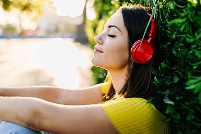 Young woman listening music through red headphones while leaning on hedge - p300m2293963 by Xavier Lorenzo