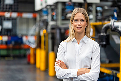 Smiling businesswoman with arms crossed standing at industry - p300m2299106 by Daniel Ingold