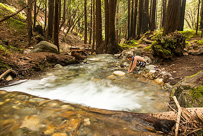 Caucasian man washing foot in forest river - p555m1482032 by Adam Hester