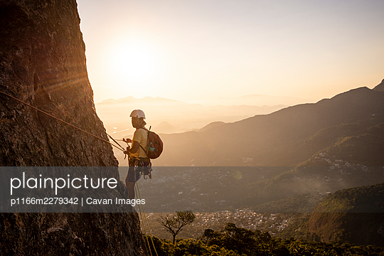 Beautiful view to male climber on steep rocky rainforest mountain - p1166m2279342 by Cavan Images