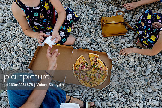 Mom and two daughters eat pizza at a picnic - p1363m2231878 by Valery Skurydin