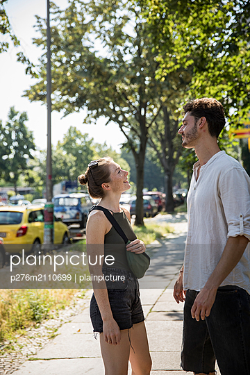 Couple is standing in front of eachother smiling  - p276m2110699 by plainpicture