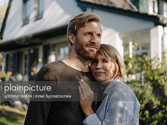 Portrait of smiling couple standing in front of their home - p300m2166614 by Kniel Synnatzschke