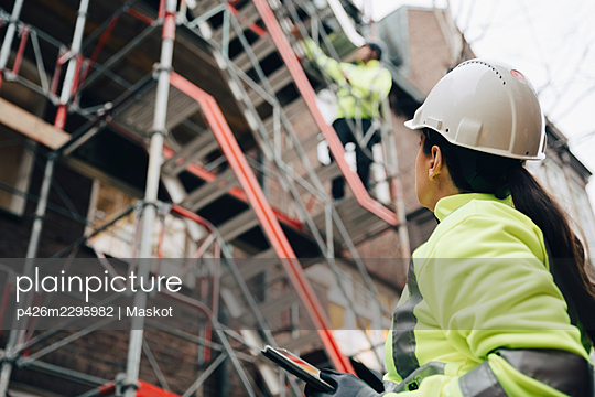 Female building contractor wearing hardhat examining construction site - p426m2295982 by Maskot