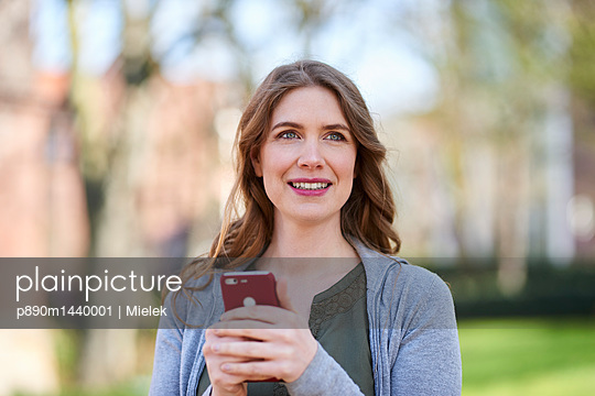 Portrait of woman in park using smartphone - p890m1440001 by Mielek