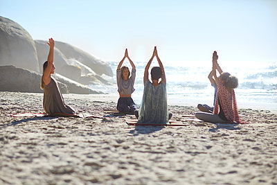 Serene people in circle meditating on sunny beach during yoga retreat - p1023m2067344 by Trevor Adeline