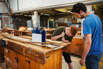 Two men standing at a workbench in a boat-builder's workshop, working on wooden joint. - p1100m1490083 by Mint Images