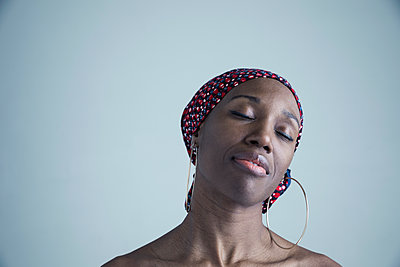 Portrait serene African American woman wearing gele headscarf and large hoop earrings with eyes closed - p1192m1213136 by Hero Images