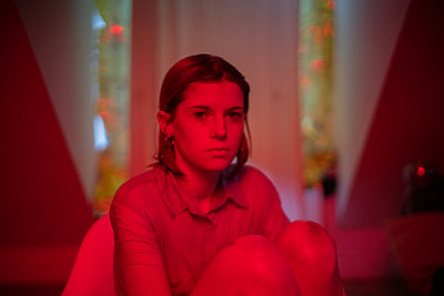 Young woman in red light - p1321m2141701 by Gordon Spooner