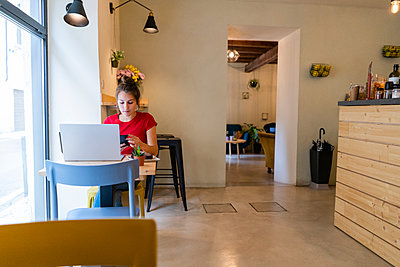 Young woman with cell phone and laptop in a cafe - p300m2139949 von Giorgio Fochesato