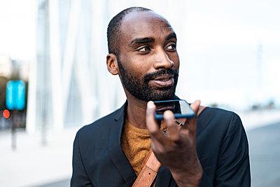 Portrait of young businessman using cell phone outdoors - p300m2160175 von Josep Suria