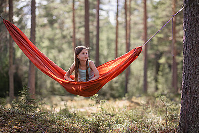 Teenage girl sitting in hammock in forest - p312m2079681 by Jonas  Gunnarsson