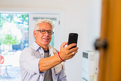 Older Hispanic artist taking cell phone photograph of art in studio - p555m1421244 by Marc Romanelli
