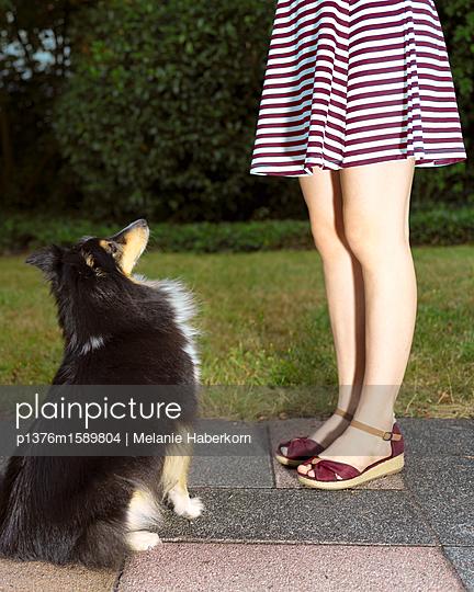 Sitzender Hund mit Mädchen - p1376m1589804 von Melanie Haberkorn